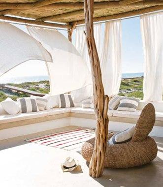 Terraza exterior cubierta con cortinas ondeando al viento. Tiene un tronco de árbol a modo de columna y un sofá de diseño con formas redondeadas.